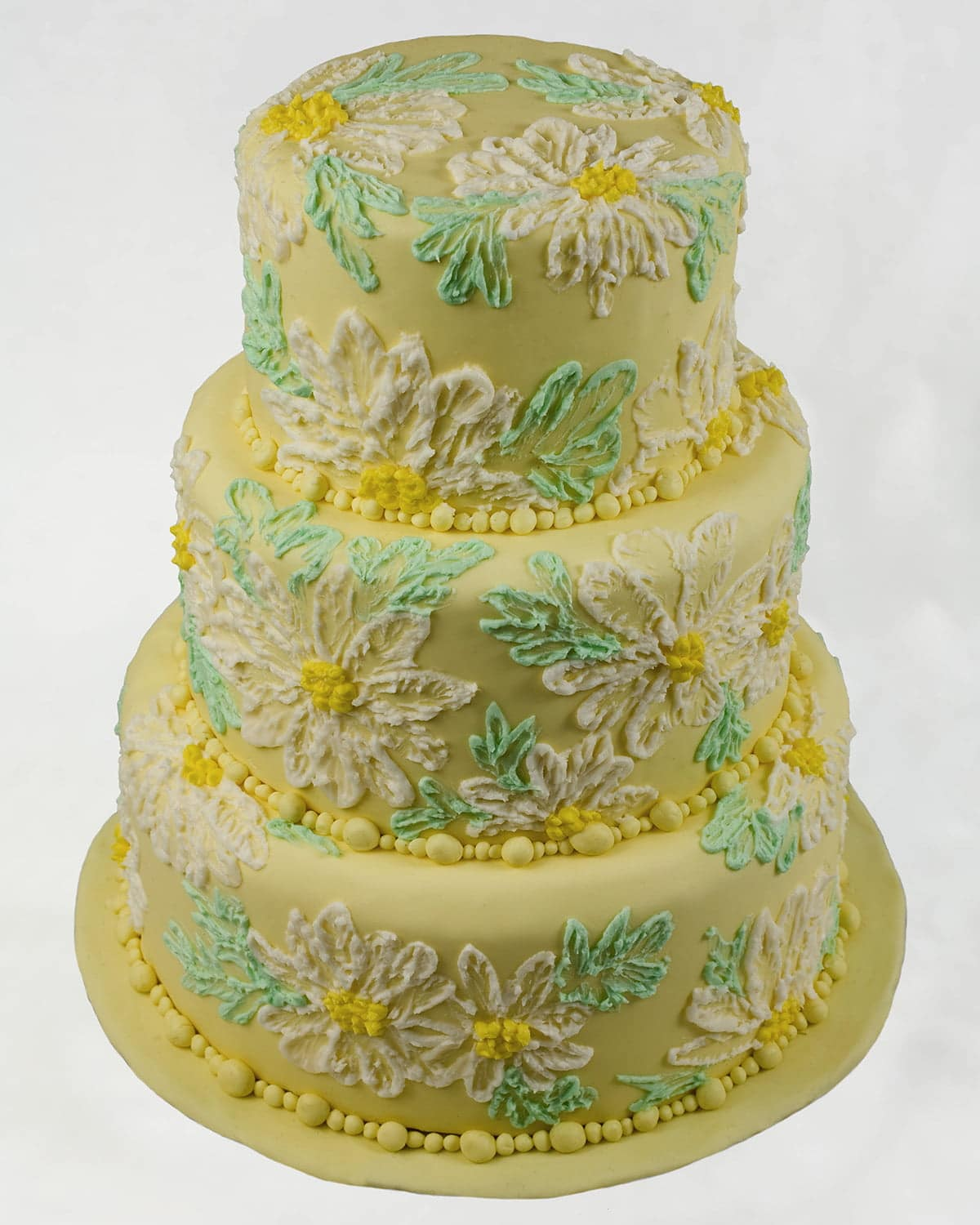 A 3 tiered round yellow cake is covered in piped daisies and leaves in whites and greens.