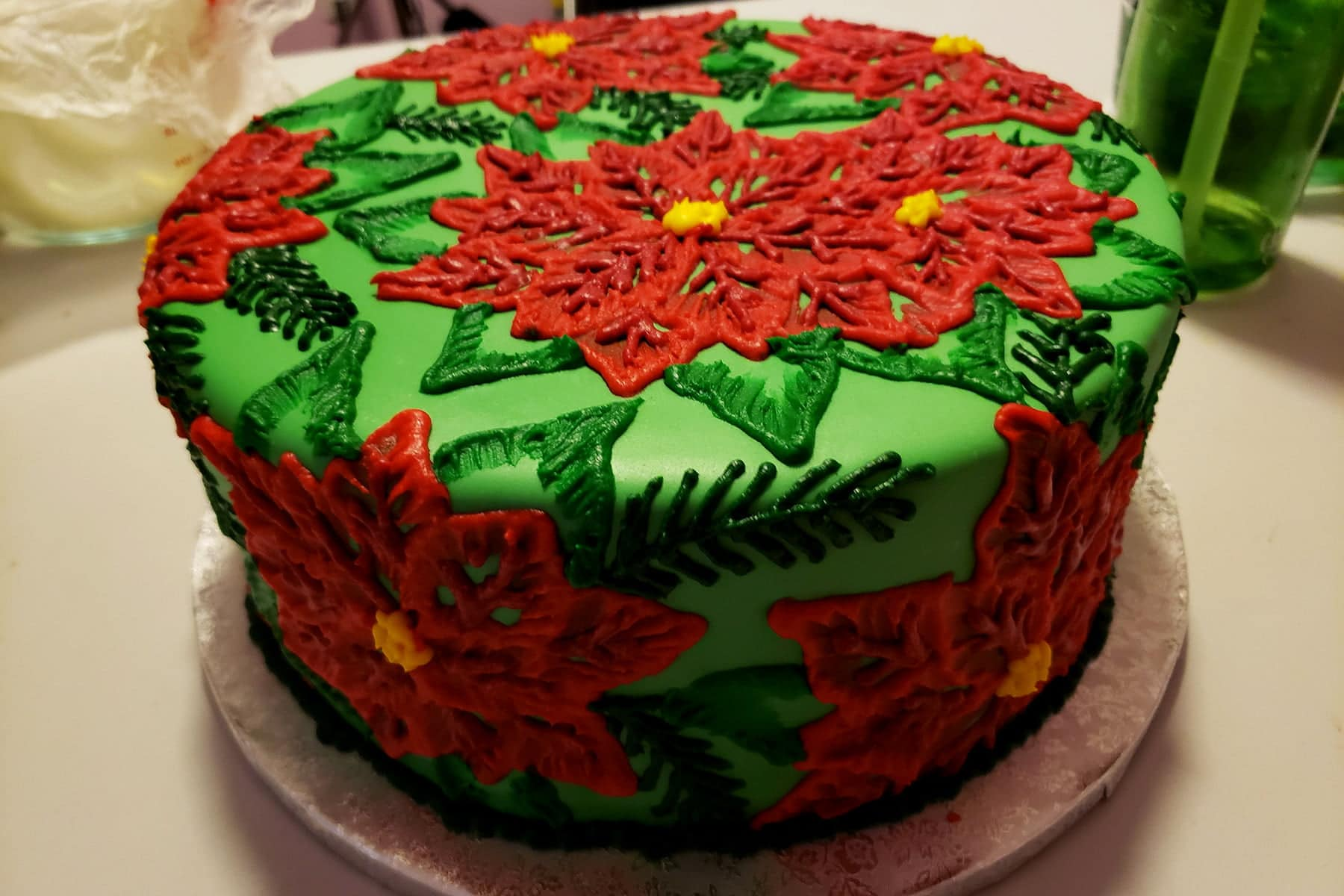 A large round cake covered in bright green fondant is covered in frosting piped to look like poinsettias. The design is mostly red and green, with accents of yellow.