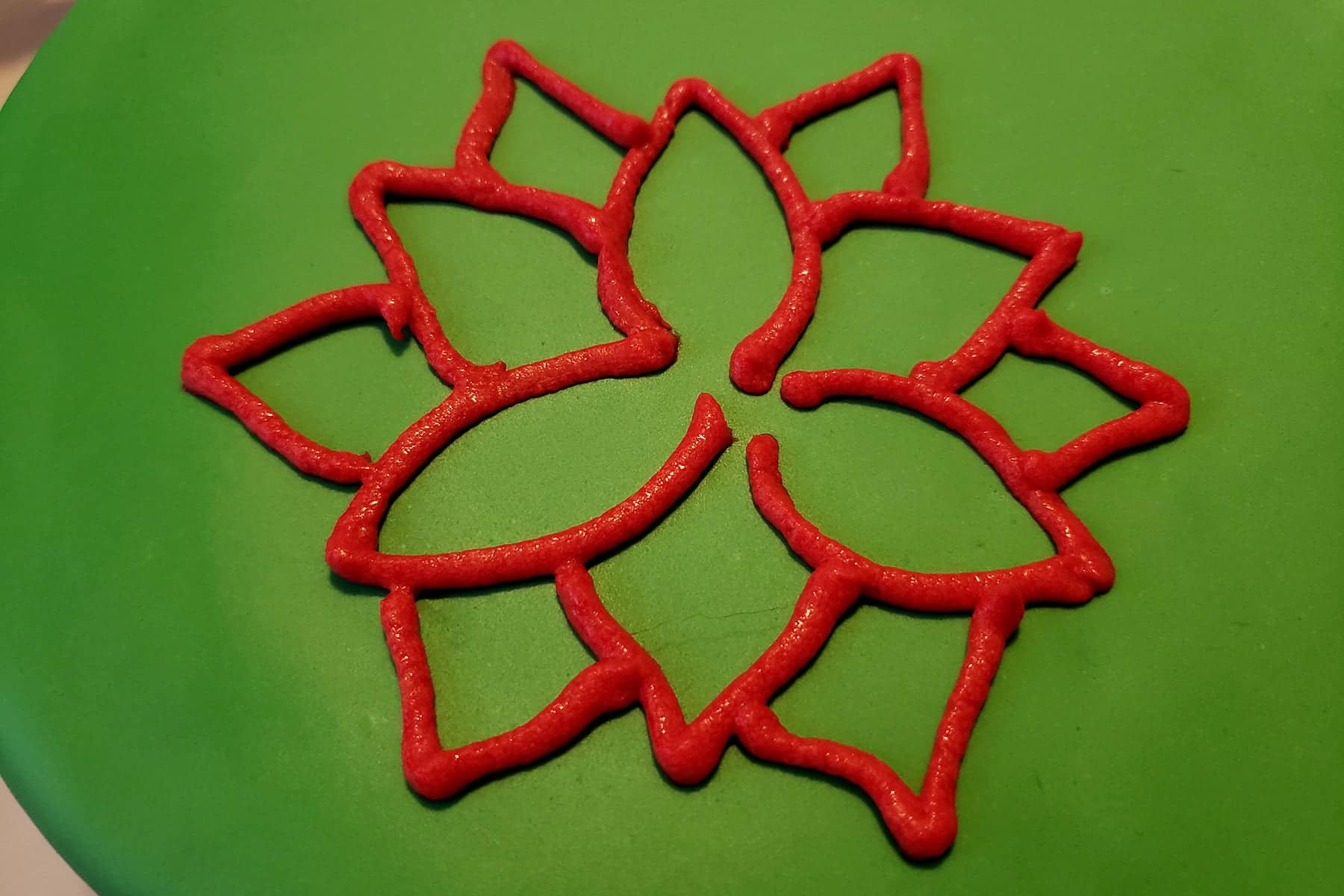 A poinsettia design has been piped in red frosting, on a background of green fondant.