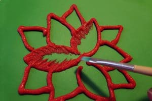 A hand uses a small paintbrush to draw frosting inward from the red piped lines that make up the poinsetta design on a backdrop of smooth green fondant.