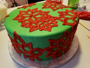 A large round cake covered in green fondant has red frosting poinsettias piped all over it.
