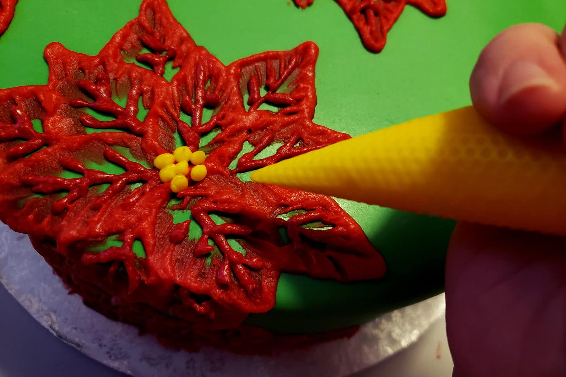 A pastry bag full of yellow frosting is being used to pipe little yellow dots in the middle of red frosting poinsettias.