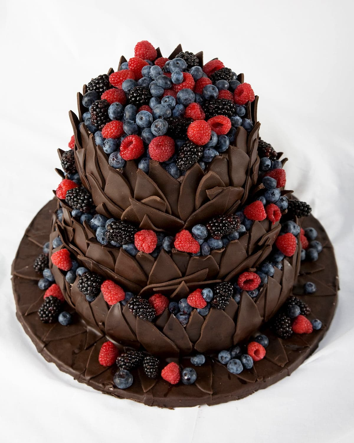 A 3 tiered cake, covered in chocolate leaves.  The top of each tier is covered in blackberries, raspberries, and blueberries.