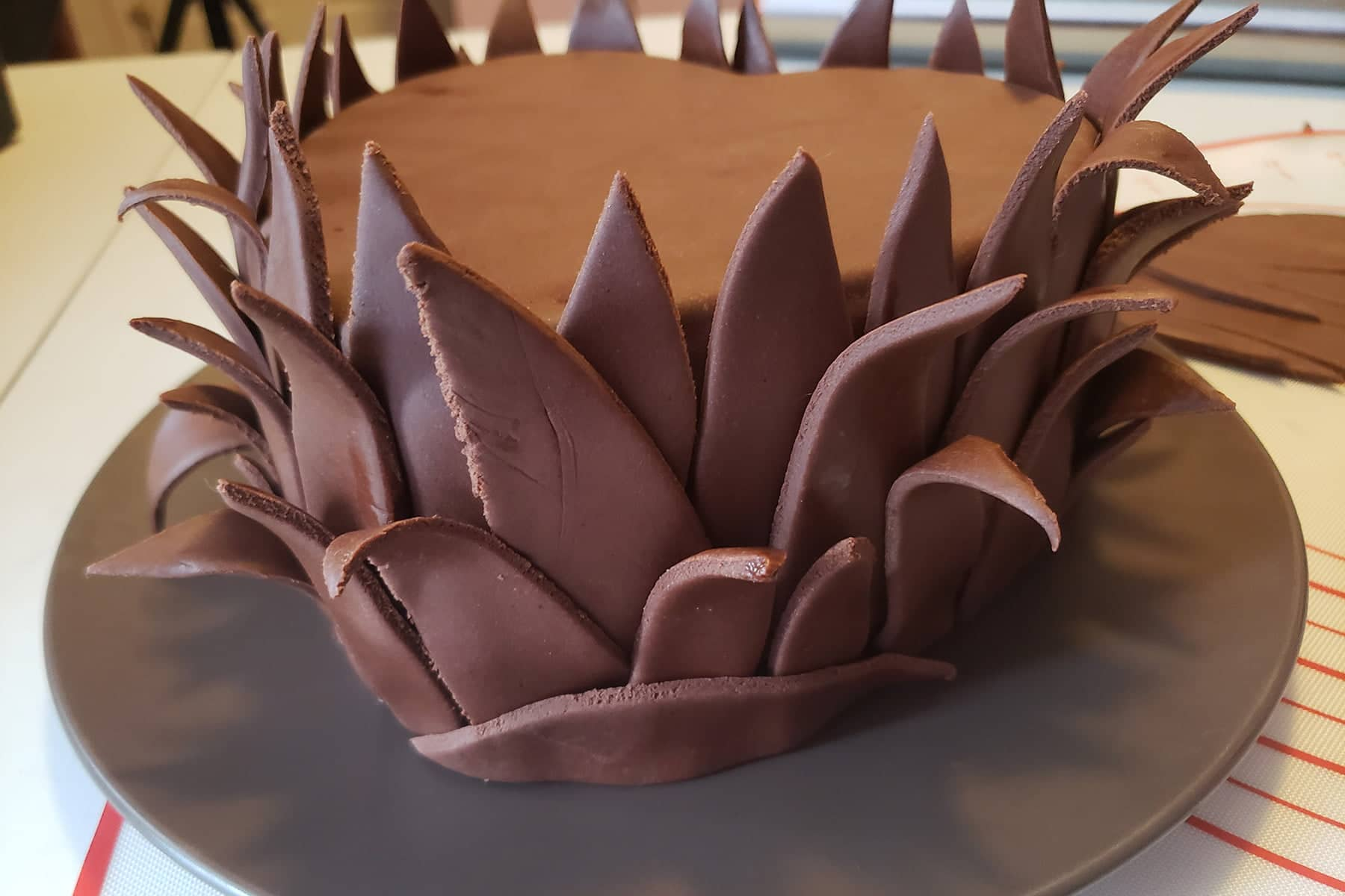 Close up view of a heart shaped cake covered in chocolate fondant. The sides have many chocolate leaves covering them, curling down on themselves.