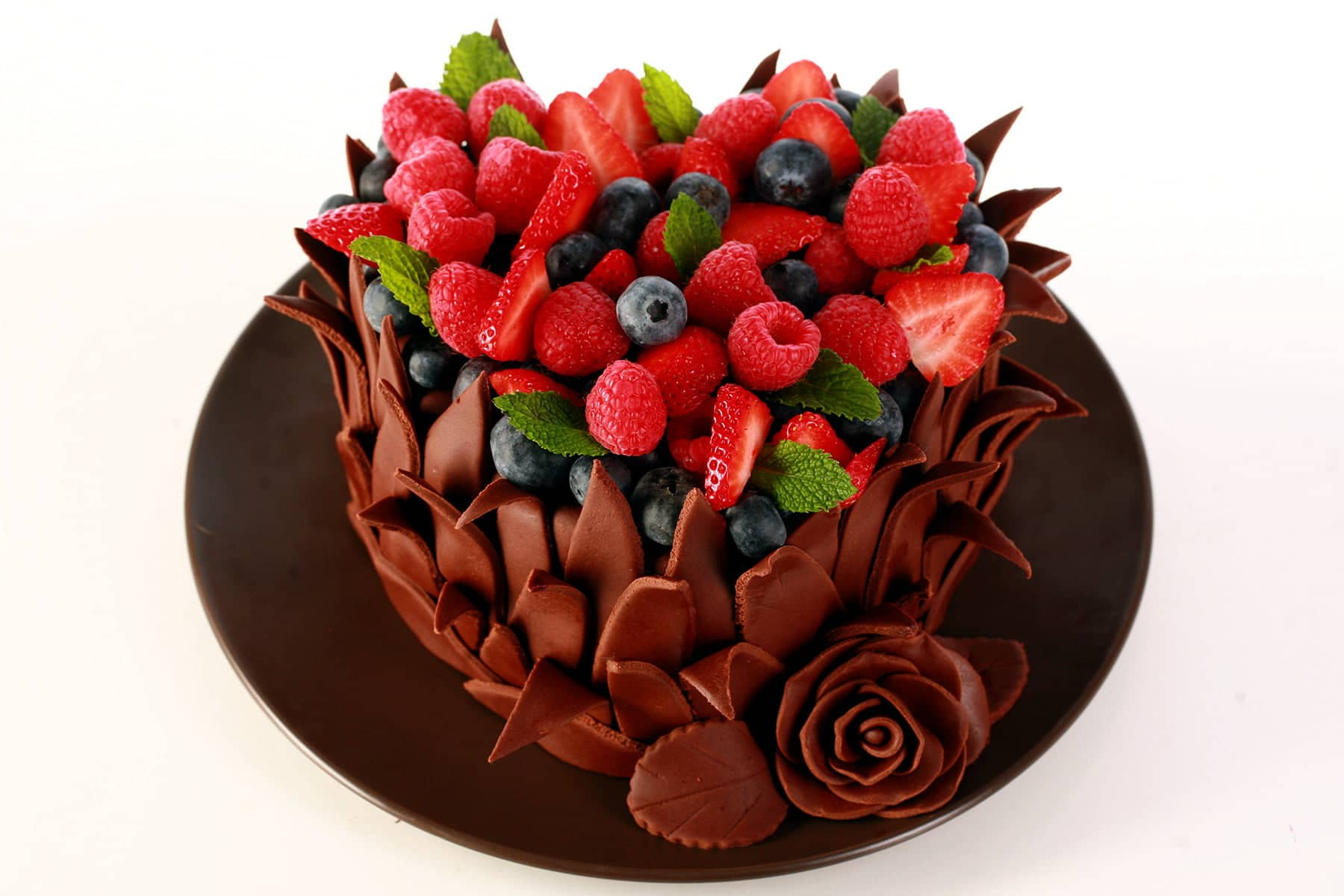 A heart shaped cake, covered in chocolate fondant leaves. The top of the cake is covered with a pile of fresh berries and mint leaves.