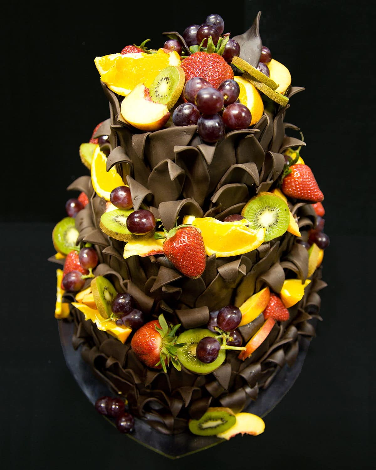 A three tiered, heart shaped cake. The sides are covered in chocolate leaves that are curling downwards, and each later is topped with a variety of fresh fruit.