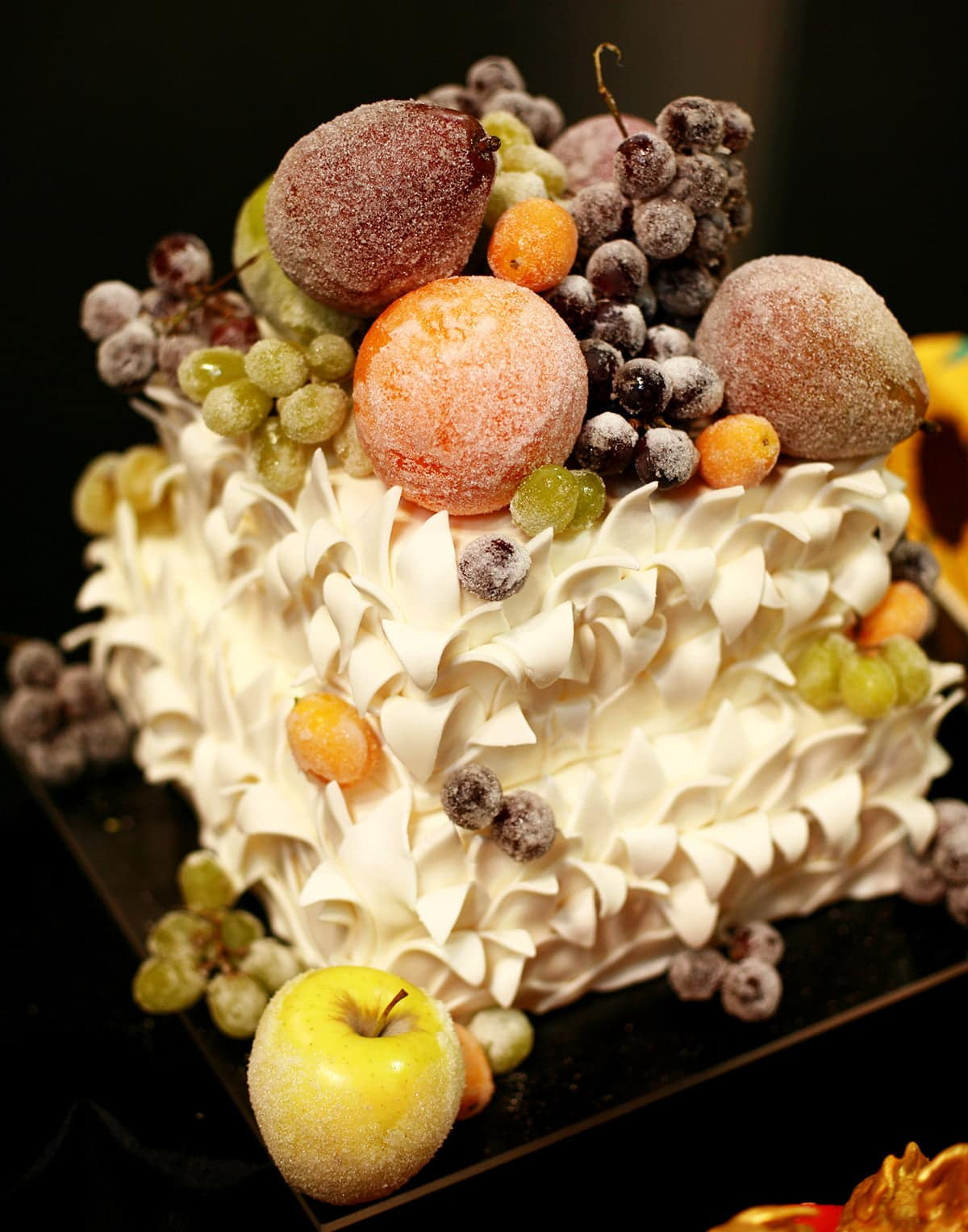 A two layered square cake.  The sides are covered in white leaves that are curling downward, and it's topped with a variety of sugar coated fruit.