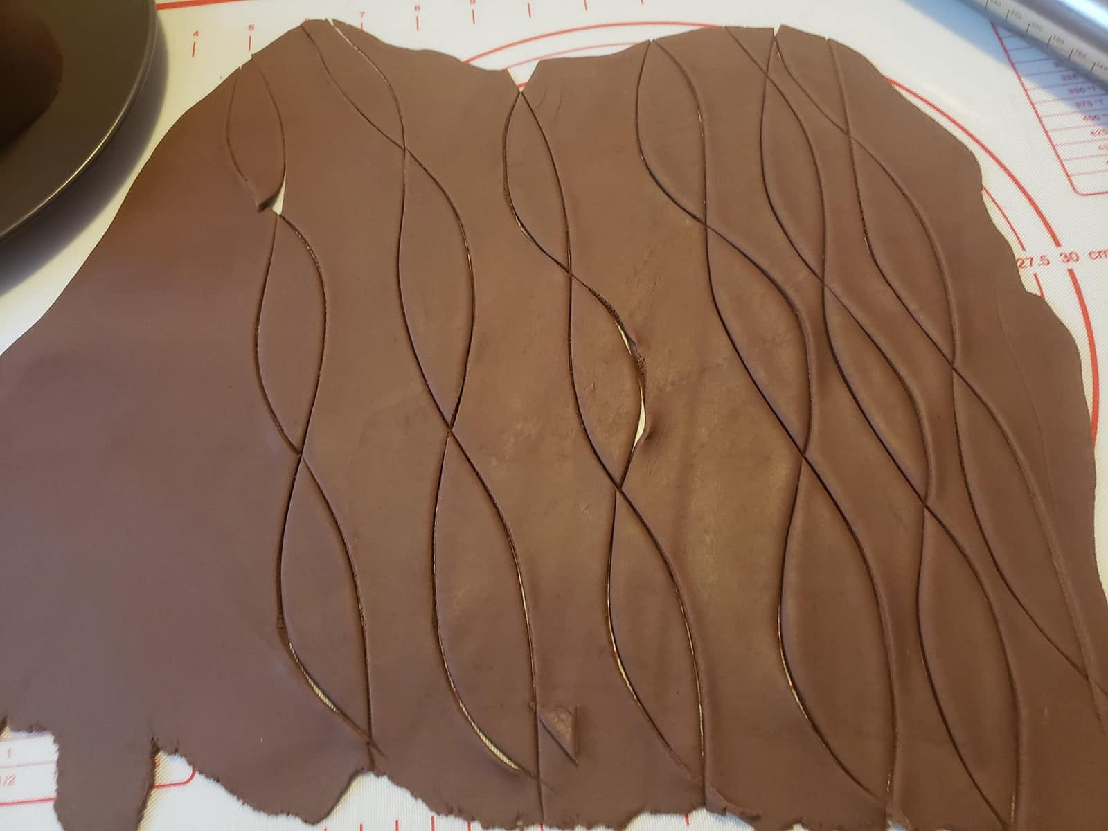 A rolled out piece of chocolate fondant, with leaf shapes cut from it.