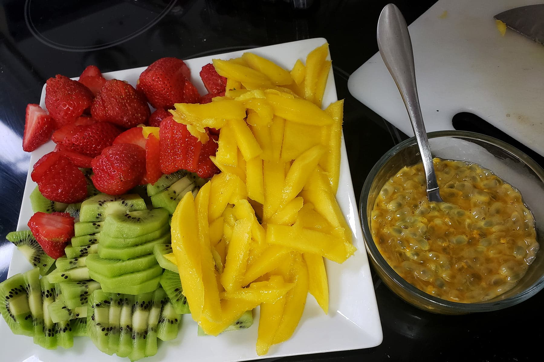 A plate of sliced mango, strawberry, and kiwi is resting next to a bowl of passionfruit guts.