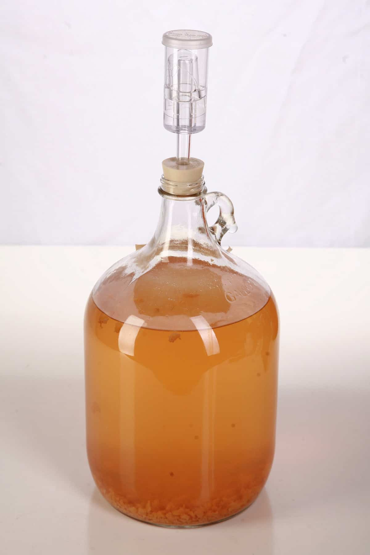 A glass carboy full of amber wine. Sediment can be seen at the bottom.