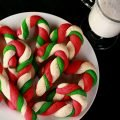 Gluten-Free Candy Cane cookies - candy cane shaped cookies, made from lengths of red, green, and white twisted dough - on a plate. There is a glass of milk behind the plate.