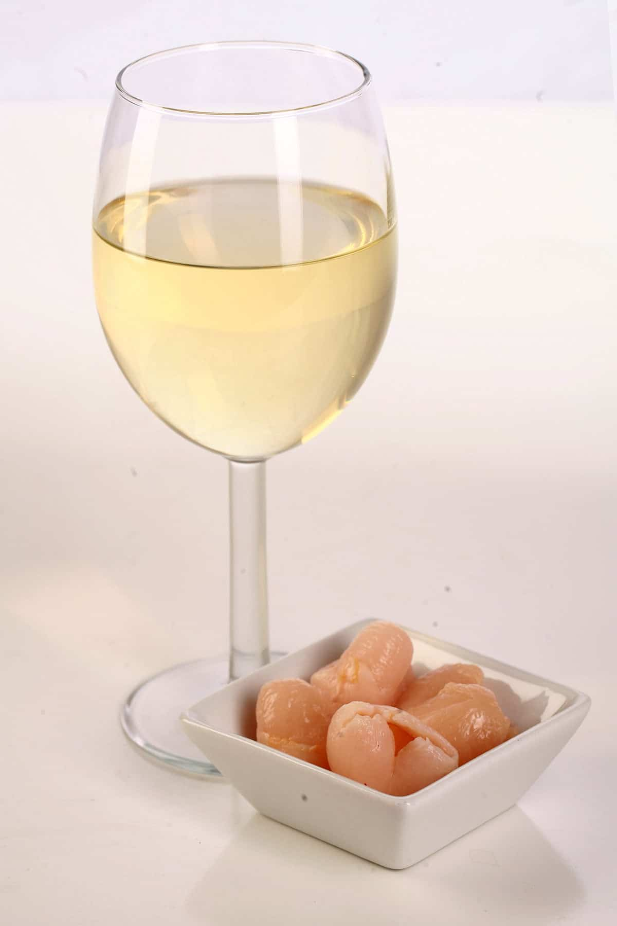 A glass of white wine  - made from this lychee wine recipe - is pictured next to a small bowl of lychee fruit.