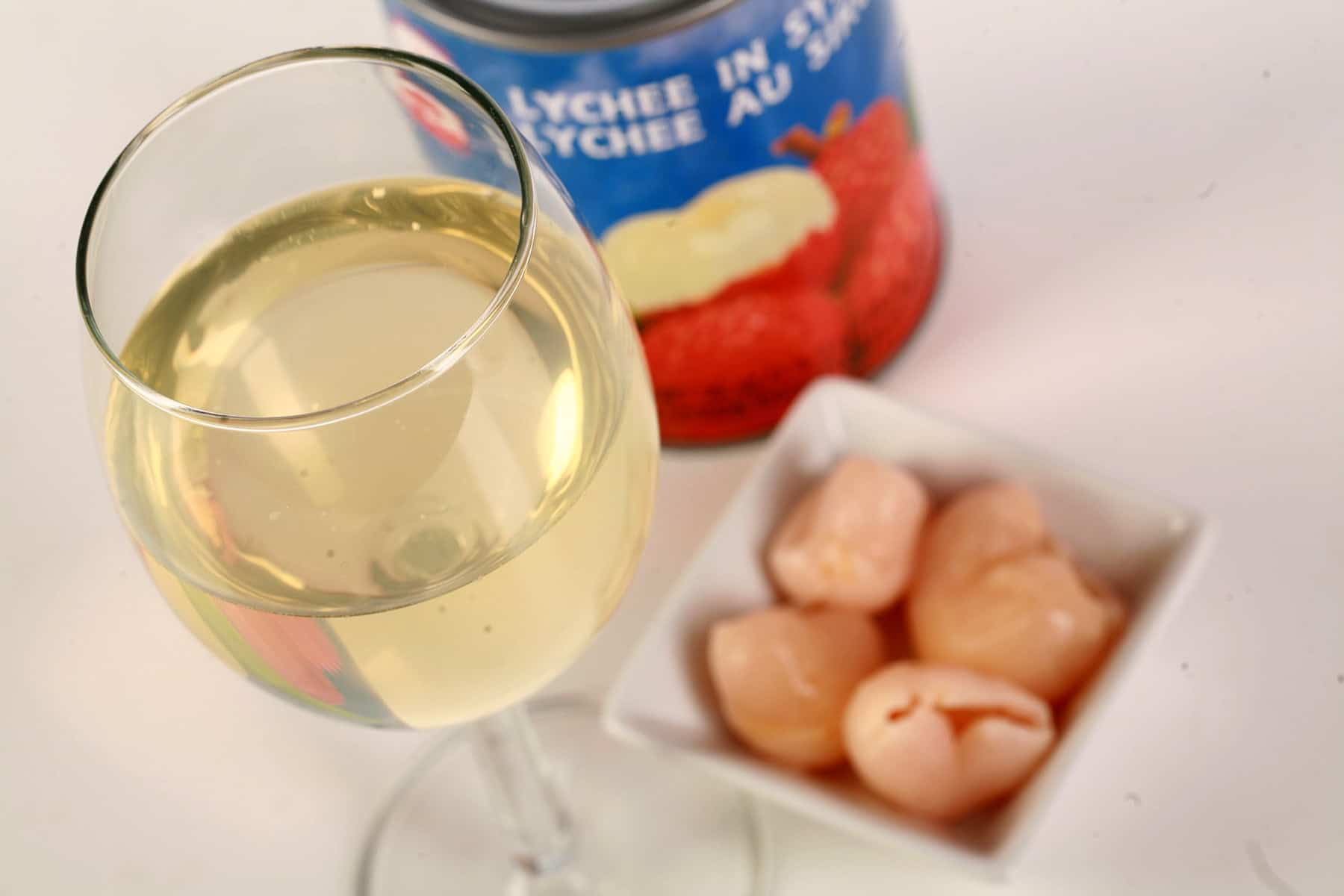 A glass of white wine is shown next to a small bowl of lychee fruit and a can of lychees.