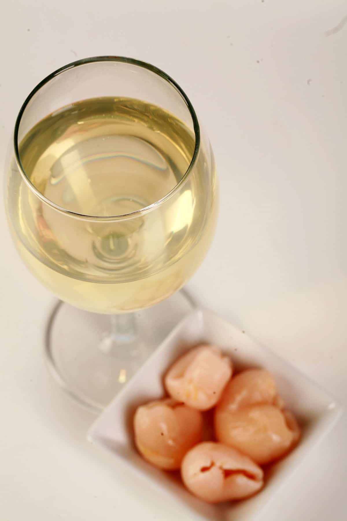 A glass of white wine is shown next to a small bowl of lychee fruit.