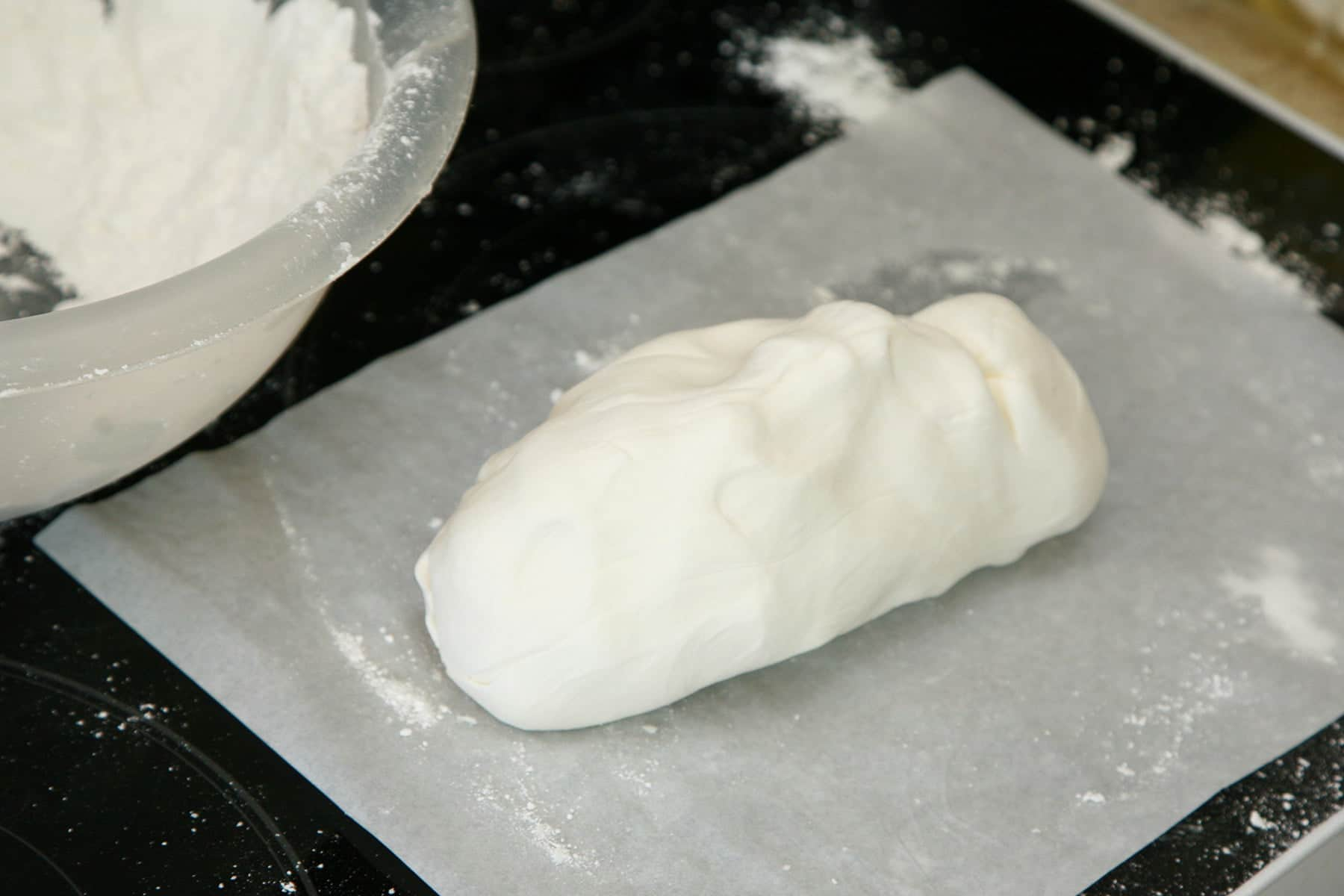 A log of smooth, white marshmallow fondant rests on a piece of parchment paper.