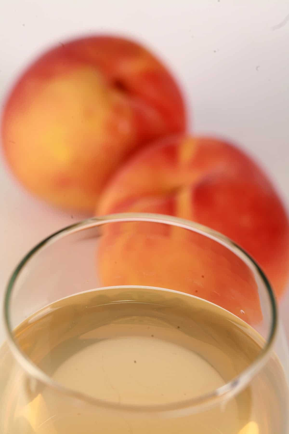 A glass of pale peach coloured wine, with 2 fresh peaches at the base of the glass.