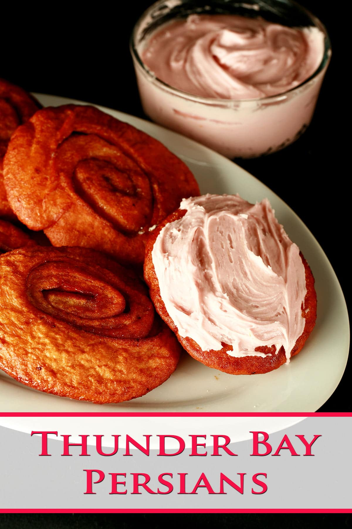 Deep fried cinnamon rolls are arranged on a white platter, one is spread with a pink frosting!
