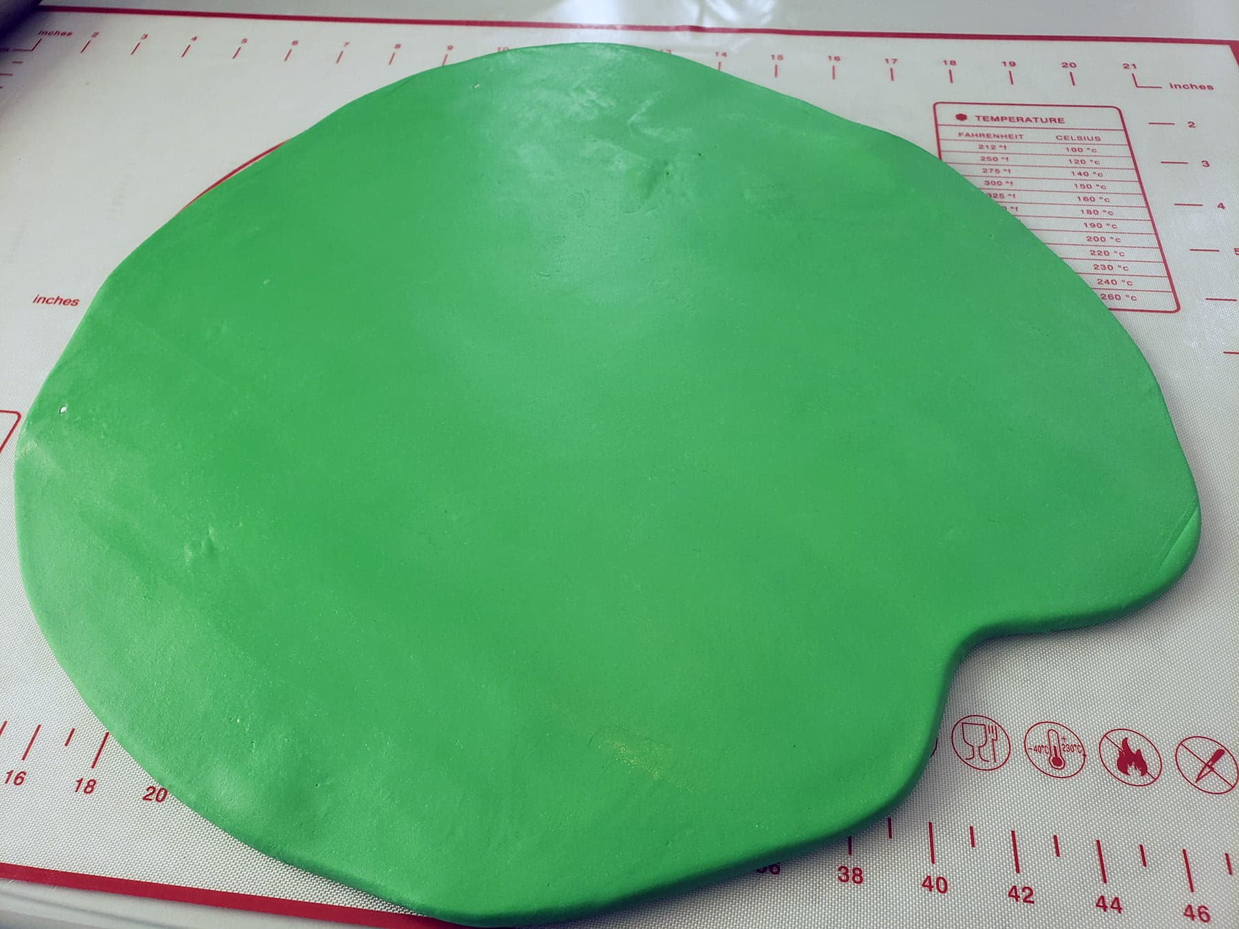 A mass of bright green fondant has been rolled out in a rough oblong shape.