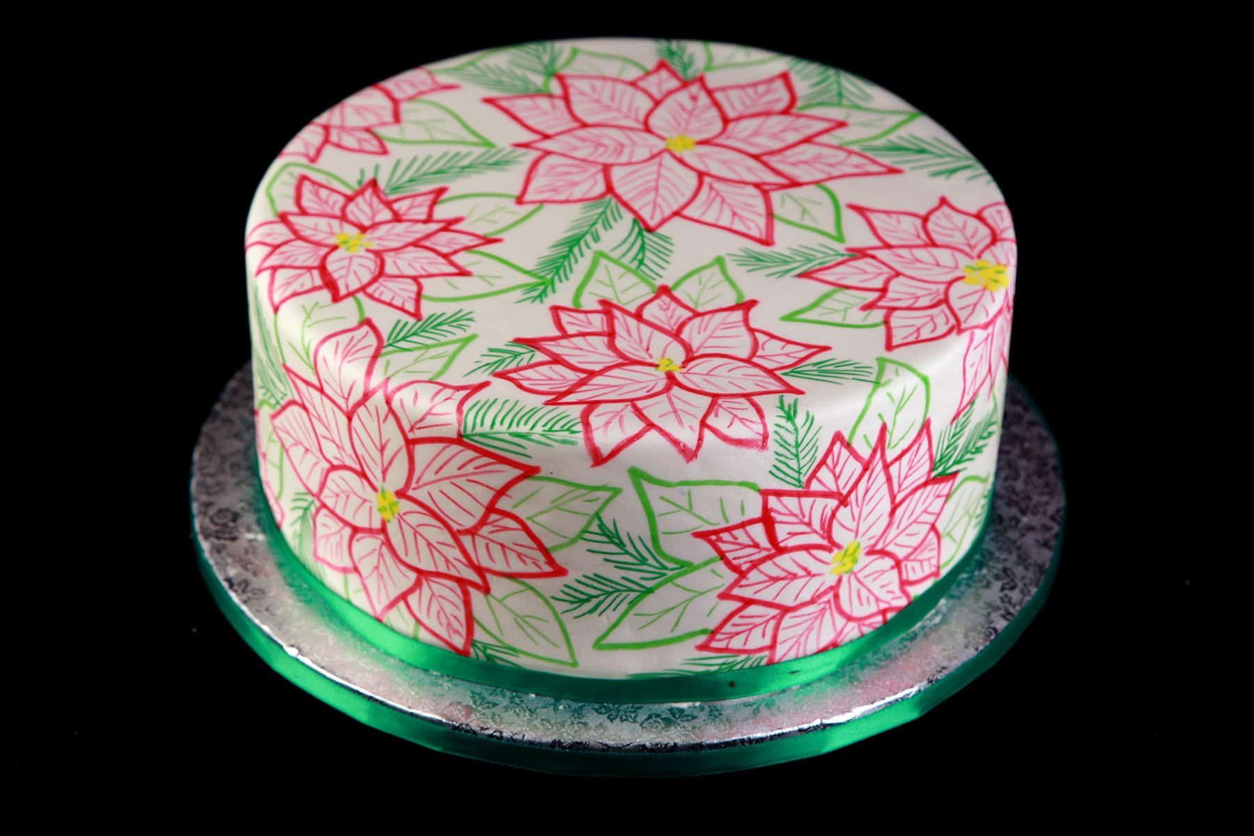 A large, round cake covered in smooth white fondant is covered in hand sketched poinsettias. The design is in red, 2 shades of green, and has yellow accents. The base of the
