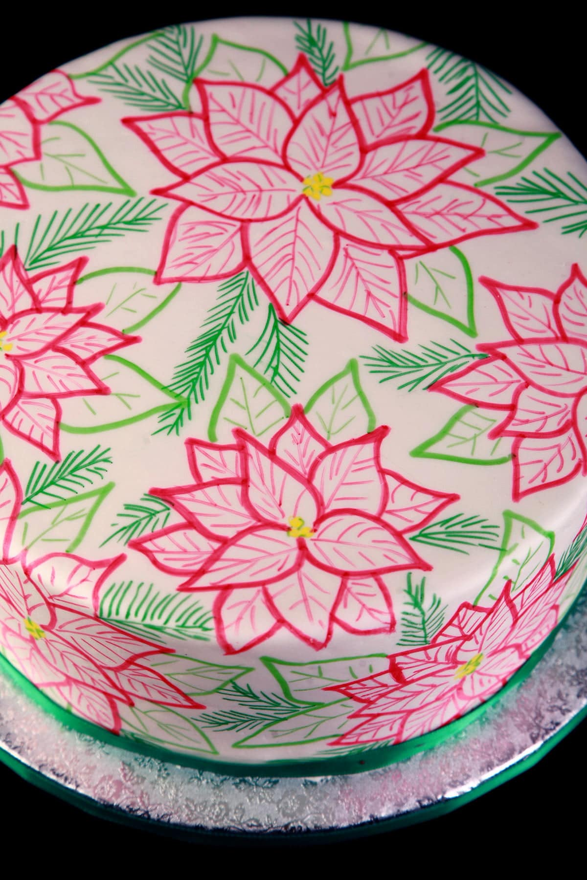 A large, round cake covered in smooth white fondant is covered in hand sketched poinsettias. The design is in red, 2 shades of green, and has yellow accents. The base of the cake is wrapped with green satin ribbon.