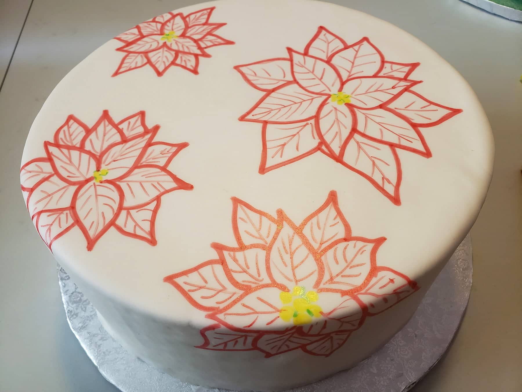A large round cake covered in smooth white fondant hasred poinsettias drawn all over it.