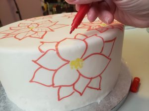 A hand uses a red food colouring marker to draw red poinsettias on a smooth white round cake.
