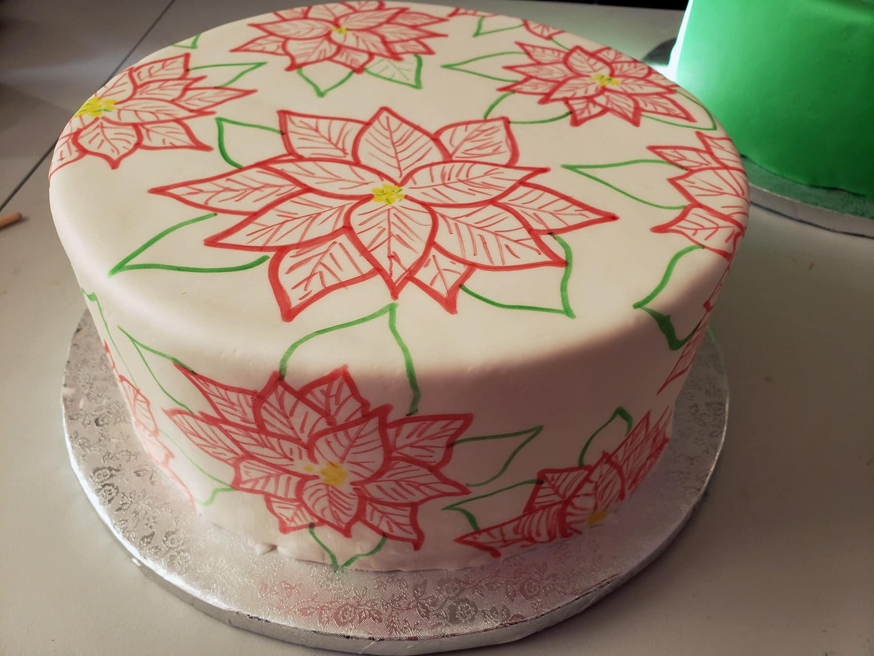 A large round cake covered in smooth white fondant has red poinsettias and green leaves drawn all over it.