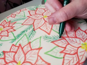 A hand uses a dark green marker to add greenery to a white cake that has red poinsettias drawn all over it.