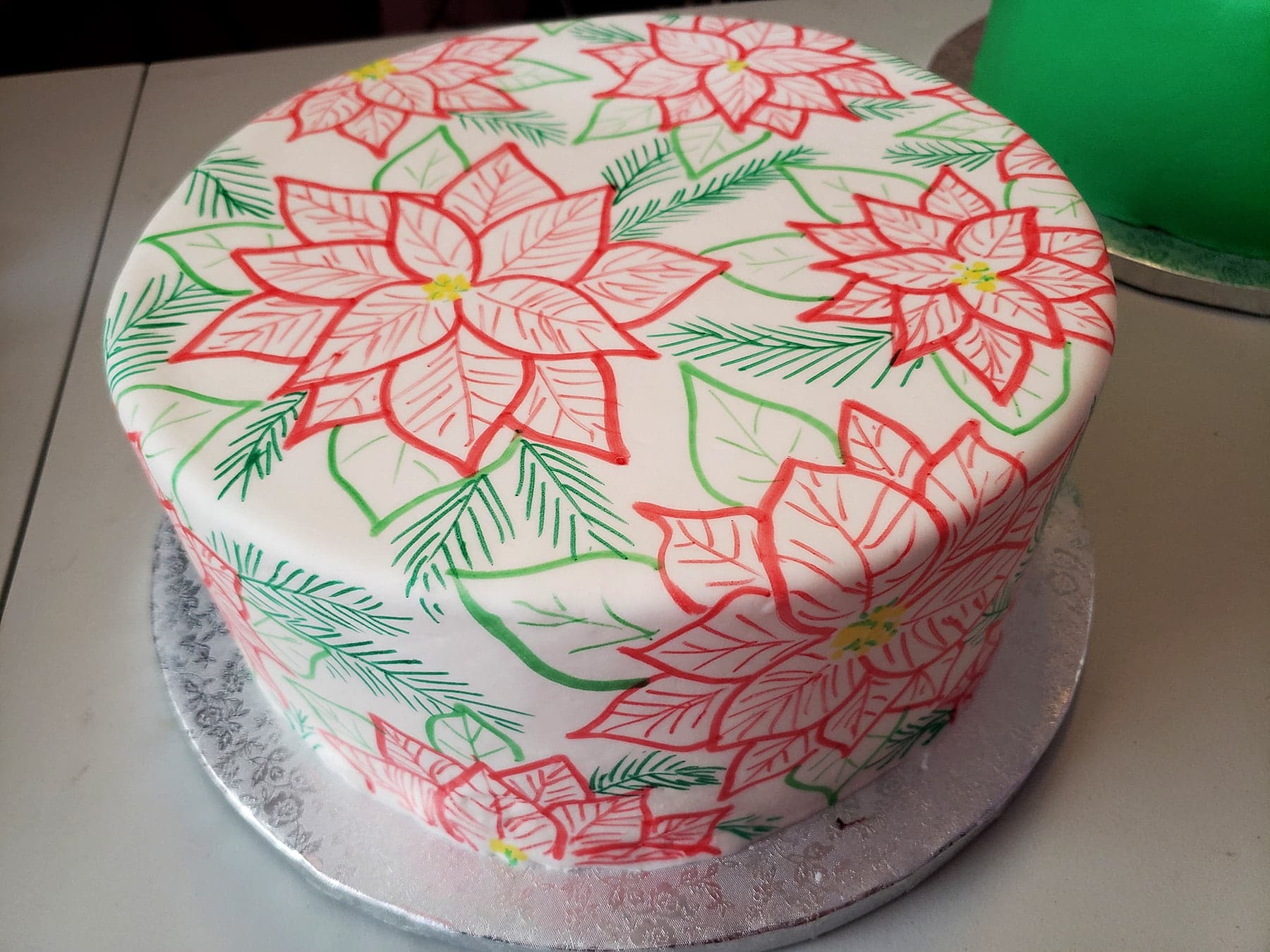 A large, round cake covered in smooth white fondant is covered in hand sketched poinsettias. The design is in red, 2 shades of green, and has yellow accents.
