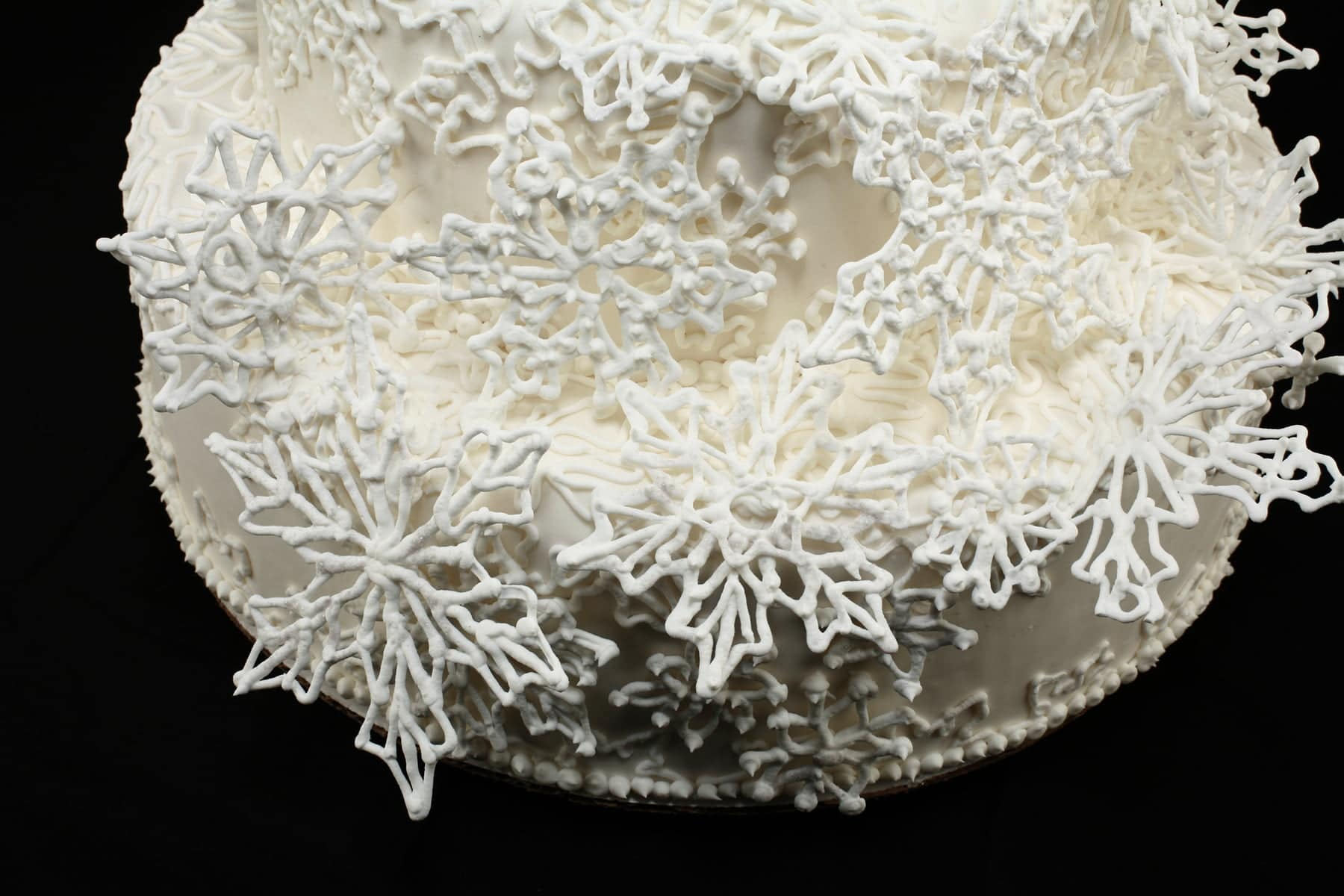 Detail photo of a 4 tier white wedding cake, piped with an intricate lace design, and adorned with a cascade of 3D piped snowflakes.