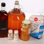 Maple syrup, a bag of sugar, and a jar of honey are pictured with a large glass bottle with deep amber coloured wine in it, as well as two small plastic bottles in front of it. These are the items needed to stabilize and back sweeten wine.