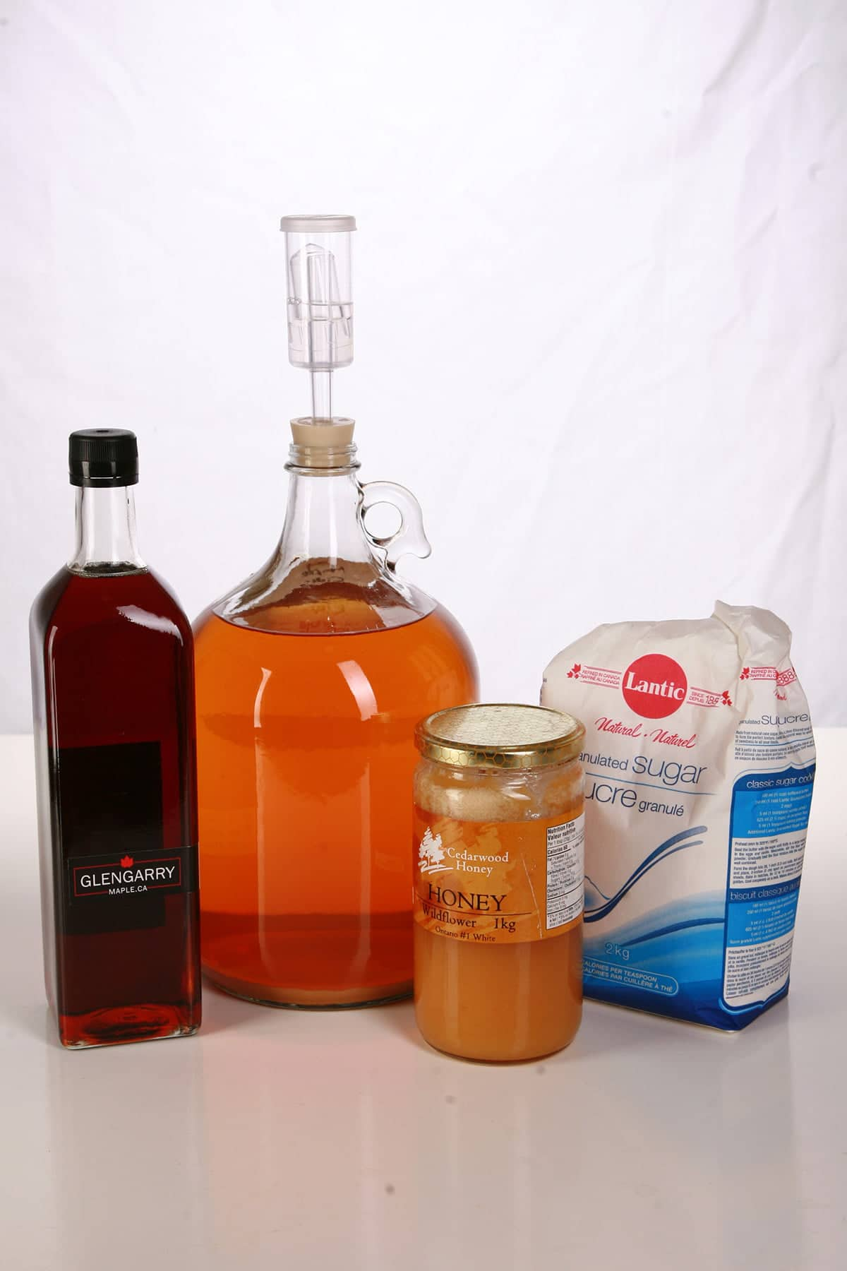 Maple syrup, a bag of sugar, and a jar of honey are pictured with a large glass bottle with deep amber coloured wine in it. These are the items needed to back sweeten wine.
