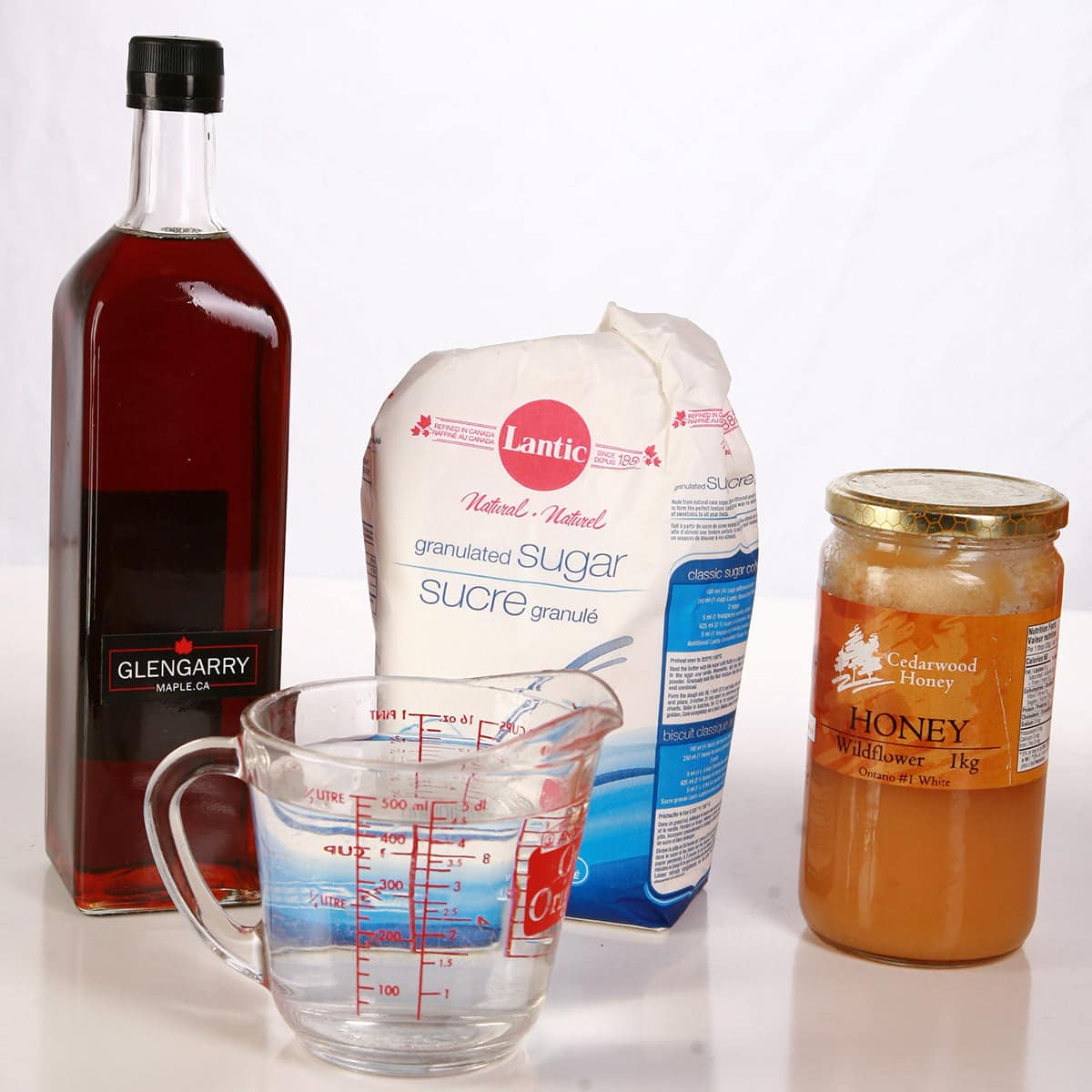 Maple syrup, a bag of sugar, and a jar of honey are pictured behind a measuring glass full of water.