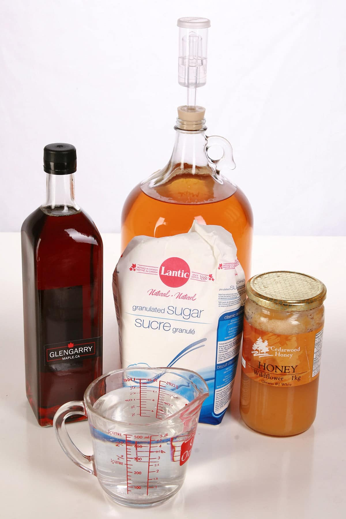 Maple syrup, a bag of sugar, and a jar of honey are pictured with a large glass bottle with deep amber coloured wine in it.