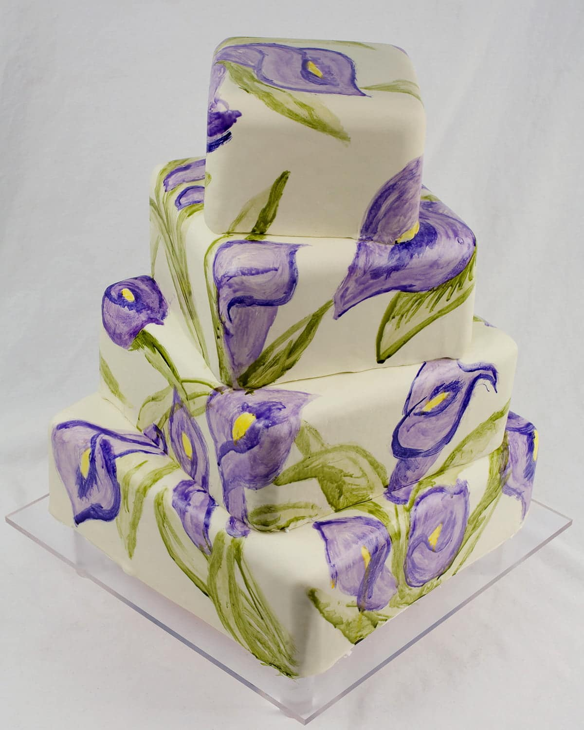 A 4 level square cake. Each layer is covered in smooth, sage green fondant, and offset from the layered above and beneath it. The entire cake is covered in hand painted calla lilies in purples and greens.