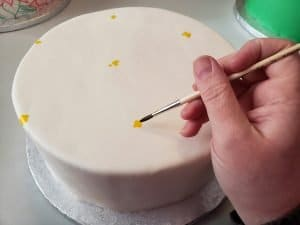 A hand uses a paintbrush to paint small dots of yellow food colouring on a smooth white round cake.