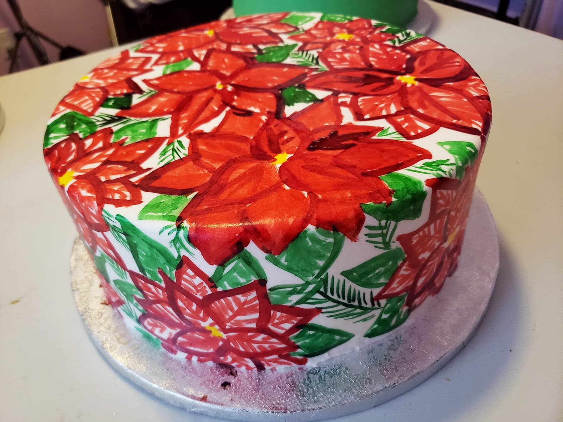 A large round cake is covered in a hand painted poinsetta design, in reds and greens.