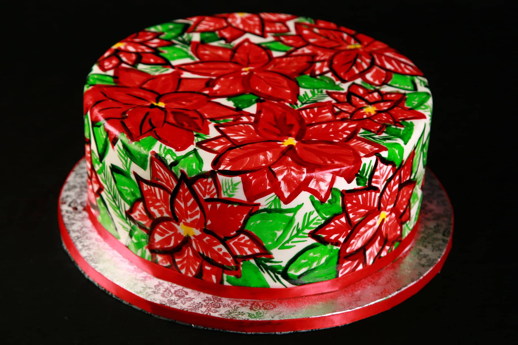 A large round cake is covered in a hand painted poinsetta design, in reds and greens. The base of the cake is wrapped with a red ribbon.