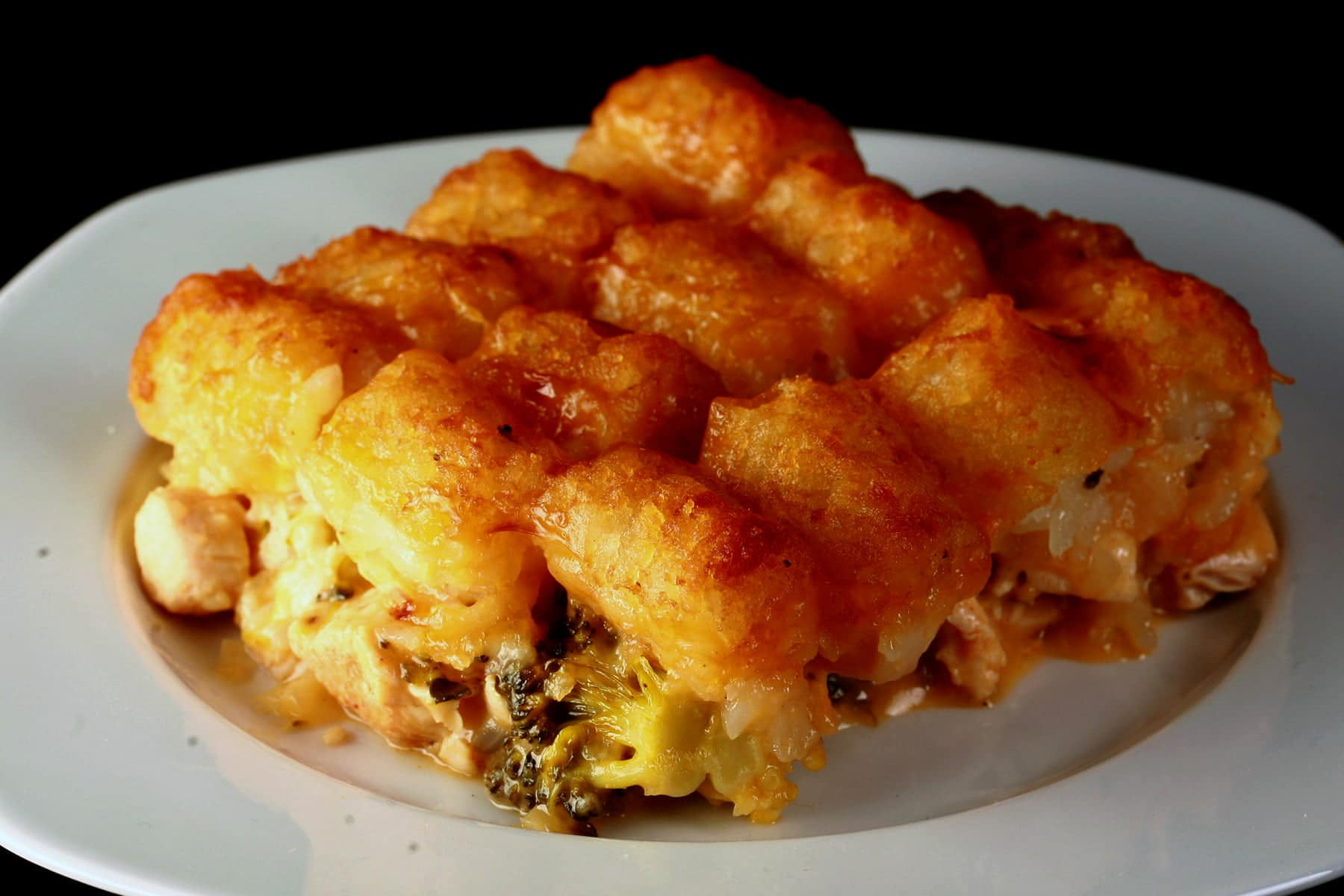 A serving of golden brown cheesy chicken broccoli tot hotdish on a white plate. Cheese and broccoli are visible in the bottom layer, covered with crispy tater tots.