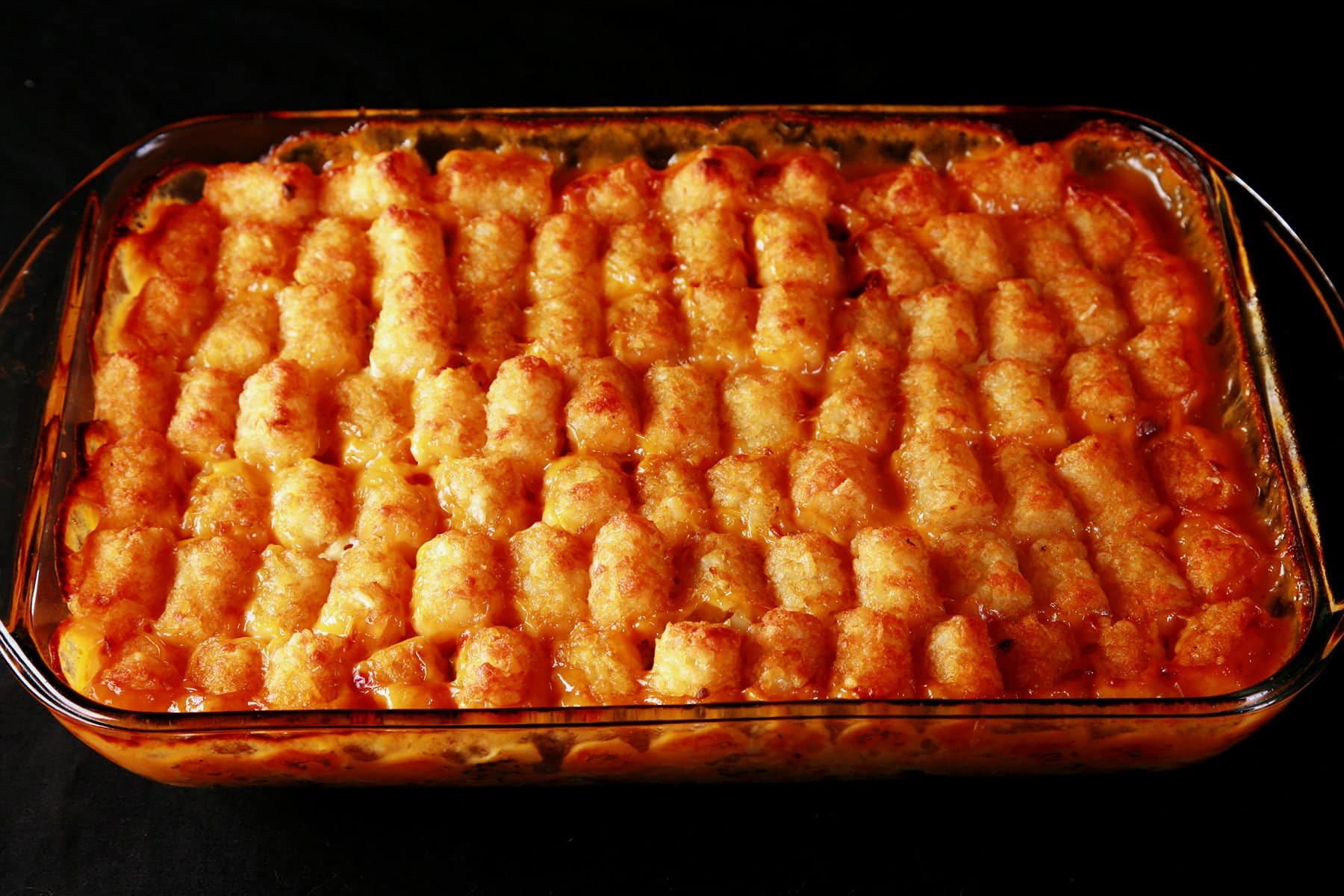 A rectangular glass baking pan with cooked tater tot hotdish.