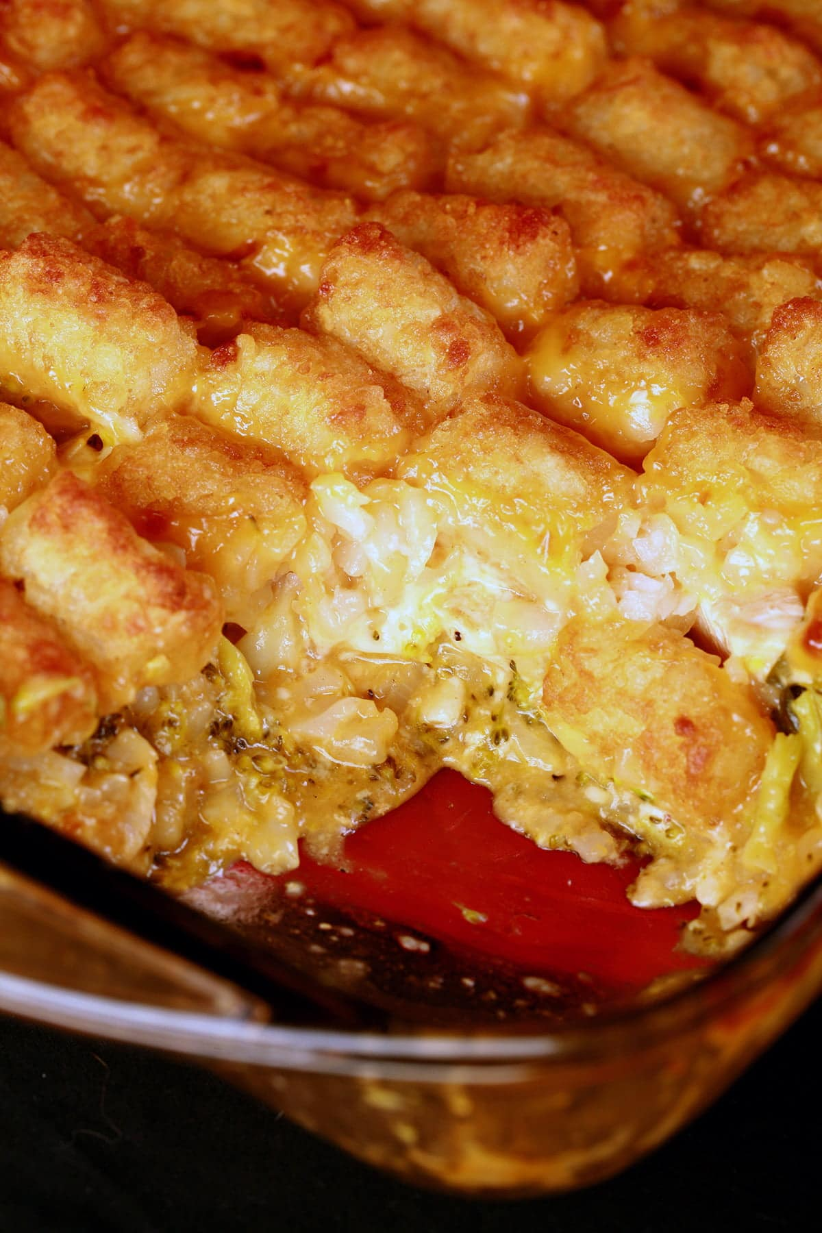 Close up view of a casserole dish with tater tot hot dish in it. One serving has been taken out, so the filling is visible.