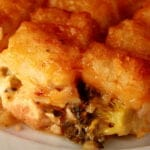 A serving of golden brown tater tot hotdish on a white plate. Cheese and broccoli are visible in the bottom layer.