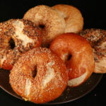 Close up photo of a small brown plate, piled with 6 large bagels, in various flavours. They were made with this How to Make Bagels tutorial.