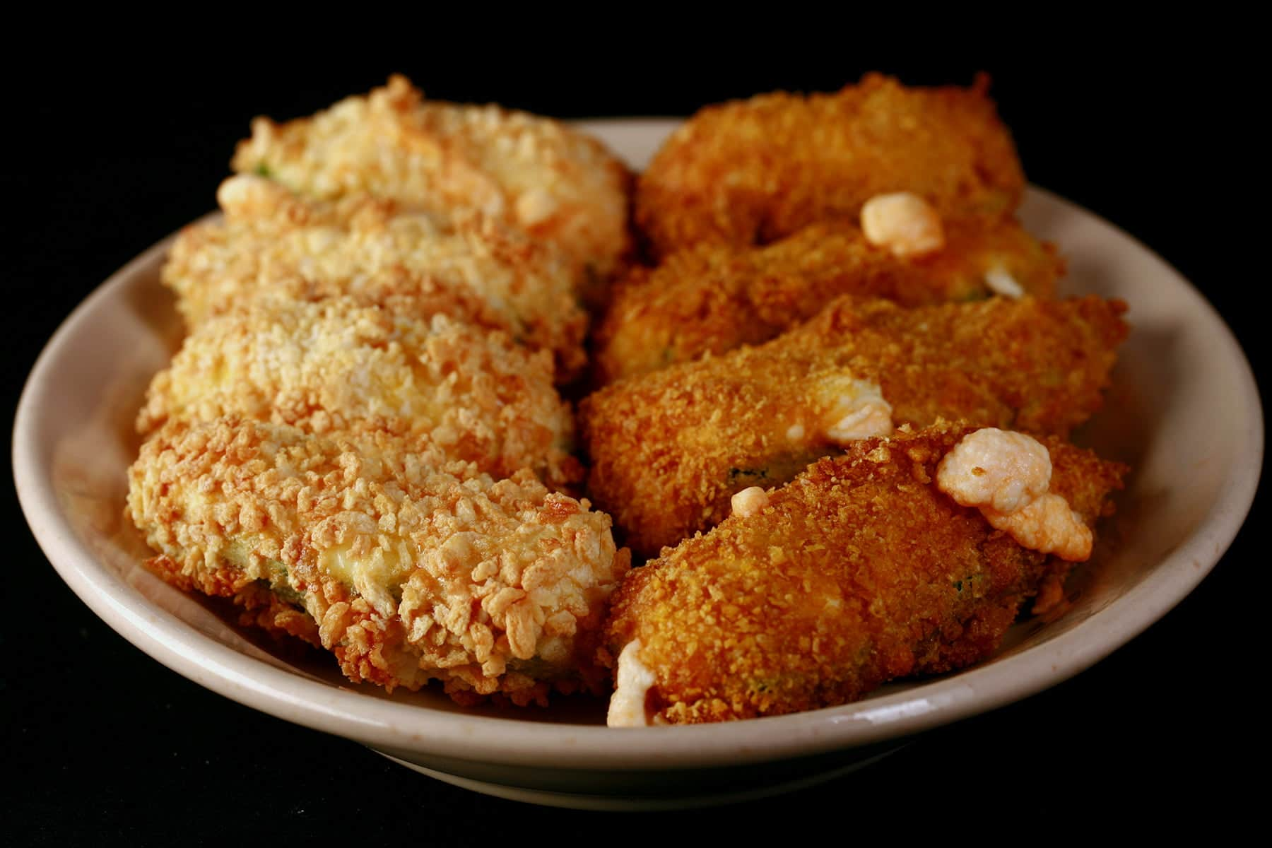 A small ivory colour plate holds two different types of gluten-free jalapeno poppers.