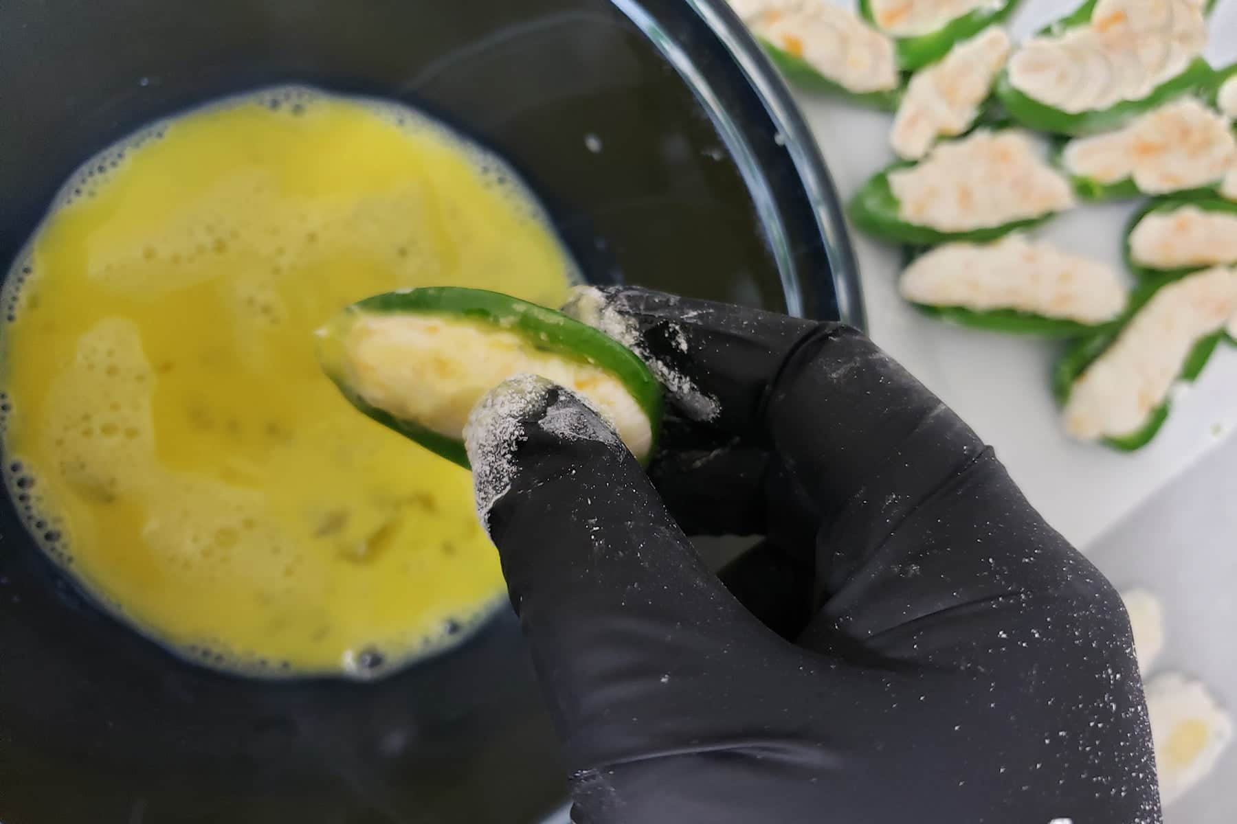 A gloved hand is shown dipping a filled jalapeno half into egg.