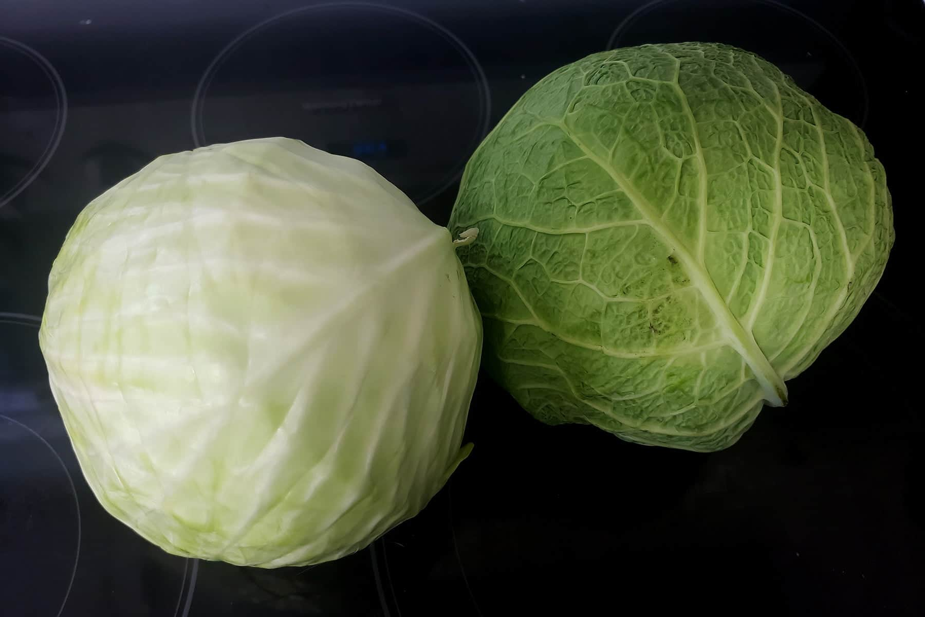 Two cabbages on a black stovetop.