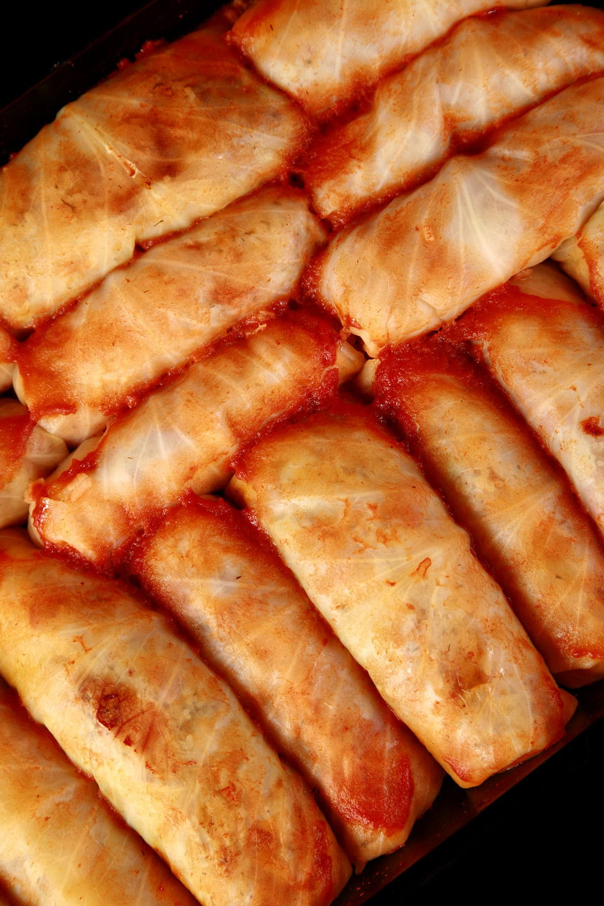 A close up view of a pan of V* covered cabbage rolls.