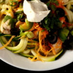 A white bowl with chicken enchilada zoodles - sauteed chicken and zuchinni noodles in salsa verde, topped with cheese, green onions, cilantro, black olives, and sour cream.