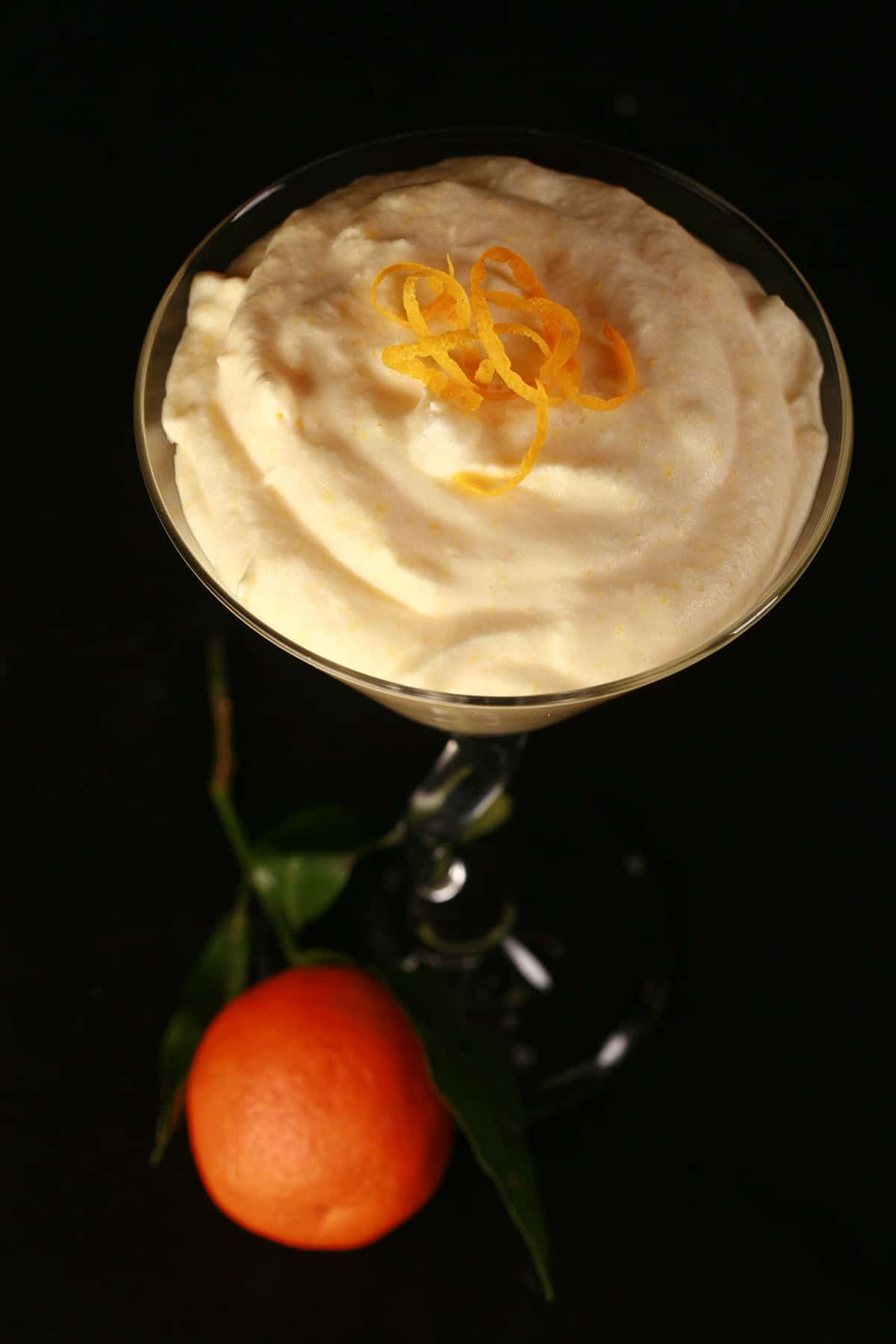 A martini glass is filled with an orange coloured clementine mousse. A clementine orange sits at the base of the glass.