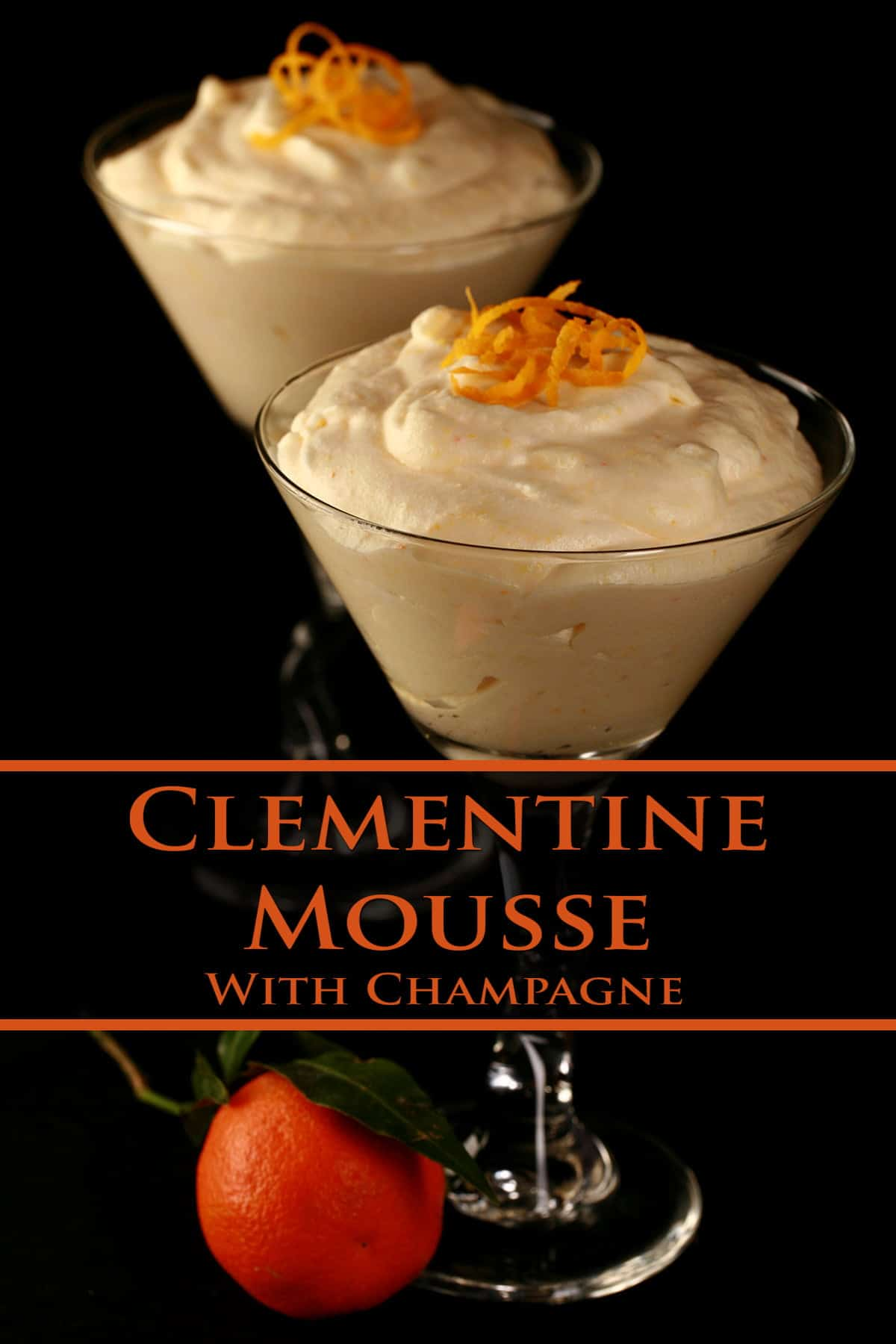 Two martini glasses, mounded with clementine-champagne mousse. There is a clementine orange near the base of one glass.